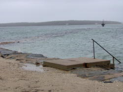Spring high tide and storm surge covers the jetty at Megansett Beach.